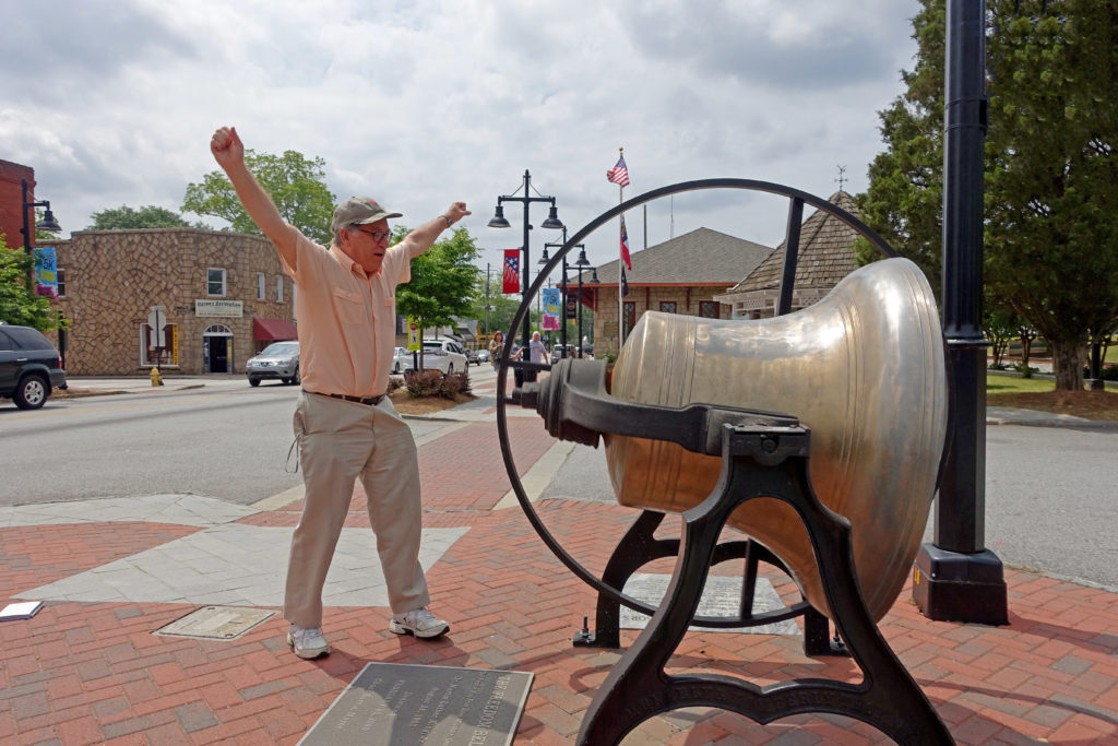 Mark Pendergrast ringing the Freedom Bell in Stone Mountain Village (it actually has no clapper).