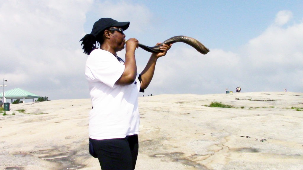 Marilyn, a Messianic Hebrew,  playing a shofar the morning of the summer solstice 2015.