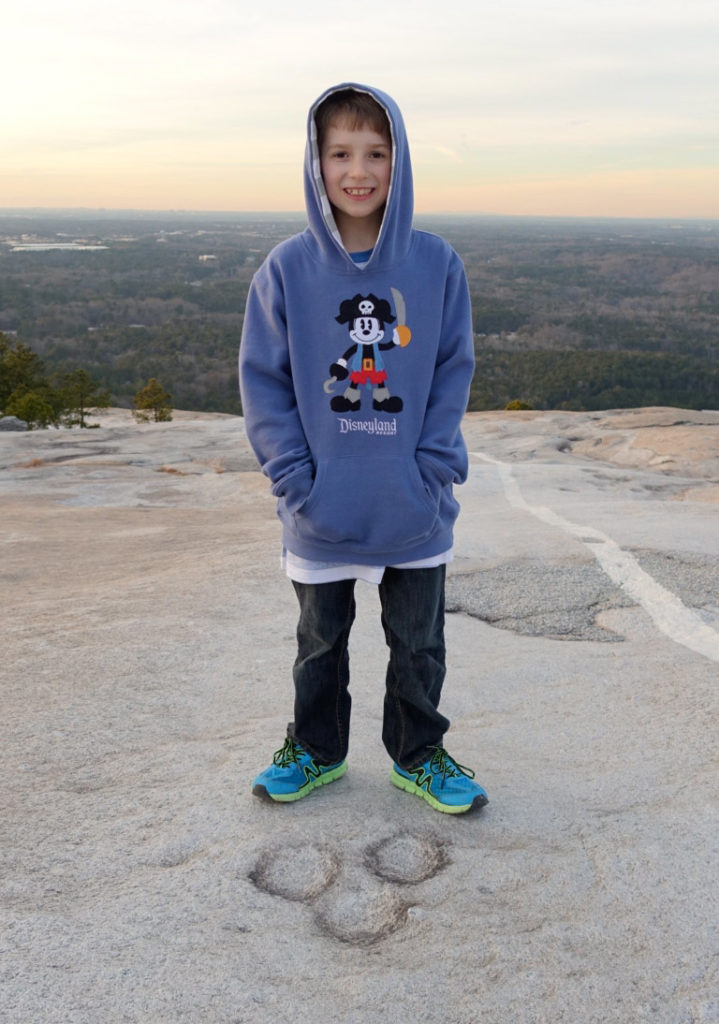 William standing near weathering pits that look like Mickey Mouse